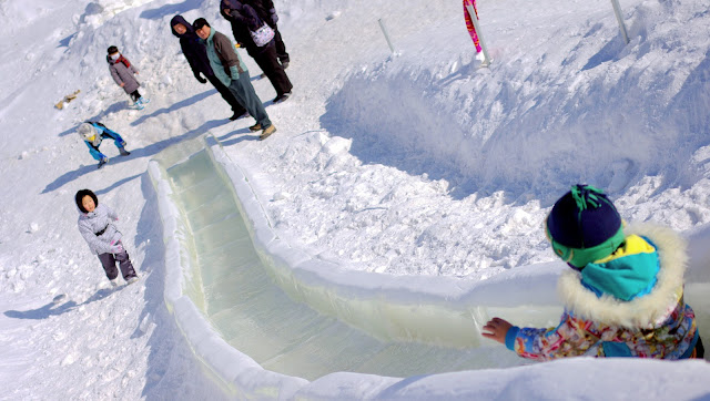 A child slides down an ice slide carved into a hillside