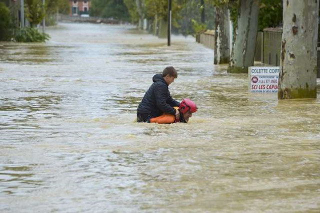 A firefighter helps a youngster to evacuate in a flooded street during a rescue operation following heavy rains that saw rivers bursting banks on 15 October 2018 in Trebes, near Carcassone, southern France. Photo: Pascal Pavani / AFP / Getty Images