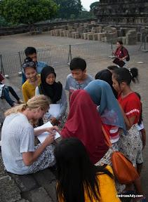 Turyście ywpełniają ankiety dla loklanej młodzieży