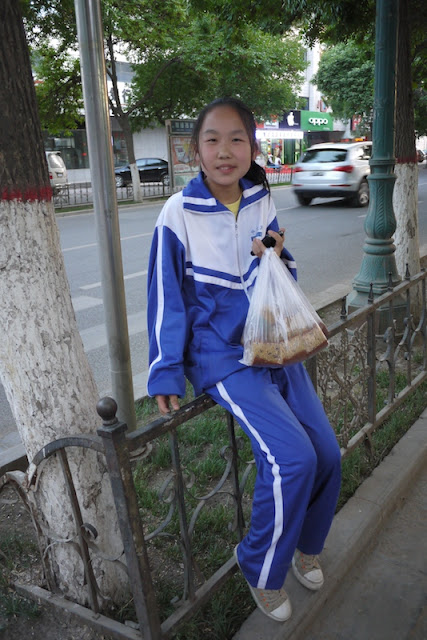 girl sitting on a rail and holding a bag of cake in Zhongwei, Ningxia