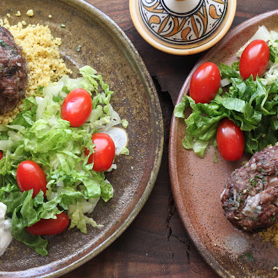 2 plates with oven baked beef kofta. Cucumber yogurt sauce, lettuce, tomato and couscous.