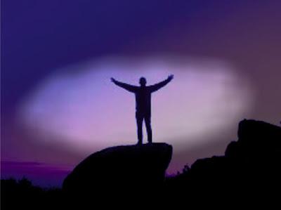 Homem encima da pedra e as mãos para o alto
