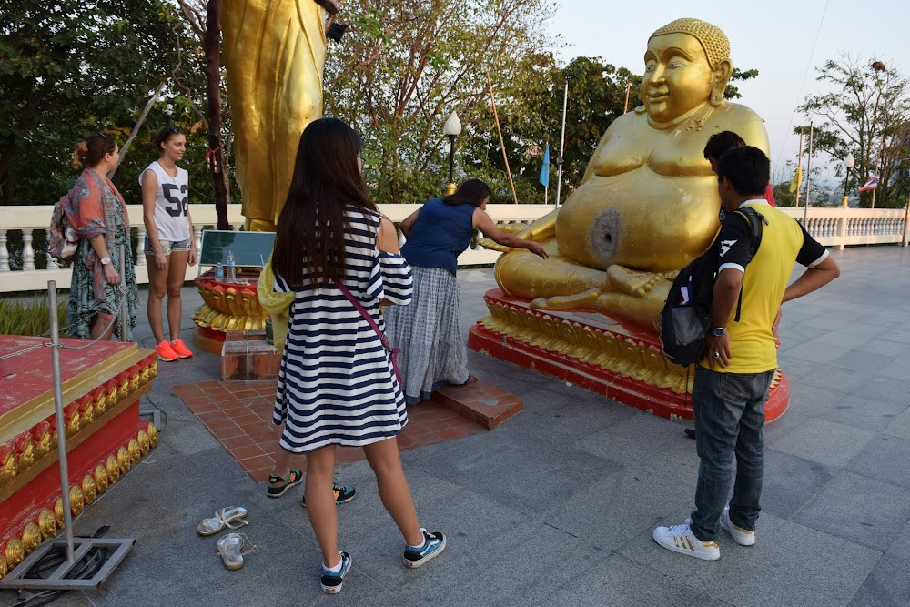 Trying to throw coins into the belly button of this fat Buddha!