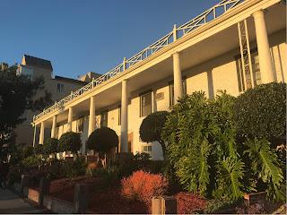 Fasaden på en hvit bygning med søyler foran hele veggen. Grønna busker i forgrunnen.