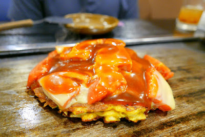 Dinner of okonomiyaki in Namba, Osaka at Ajinoya. He had the okonomiyaki with fresh tomatoes and cheese