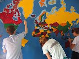 PVs work on a mural of the world