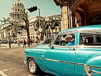 %22Liking my rims eh?!%22  It's a taxi waiting in front of the National Capitol Building or El Capitolio building in Havana.