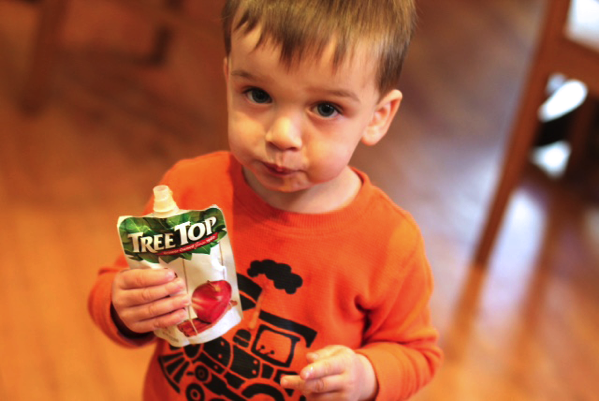 Baby enjoying tree top applesauce