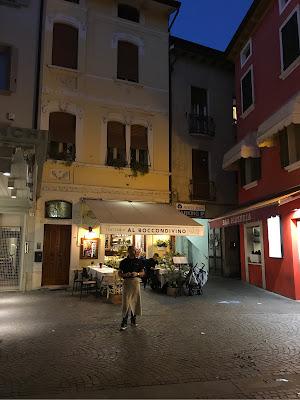 En kelner som står utenfor en liten restaurant.
