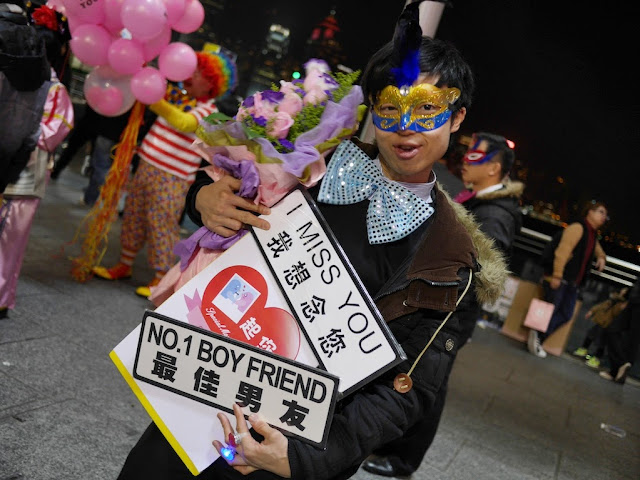 young man wearing carnival mask selling signs reading 'I miss you' and 'No.1 boy friend'