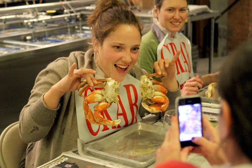 Rebecca Earie has her picture taken by Caitrin Miller with her cracked crab during a crab cracking class by Jon Rowley at Taylor Shellfish Store in Seattle, WA, Monday December 05, 2011.  (Jim Bates / THE SEATTLE TIMES)  116947 JB: JON ROWLEY TEACHES A CLASS ON THE PROPER WAY CRACK A CRAB AT TAYLOR SHELLFISH MARKET