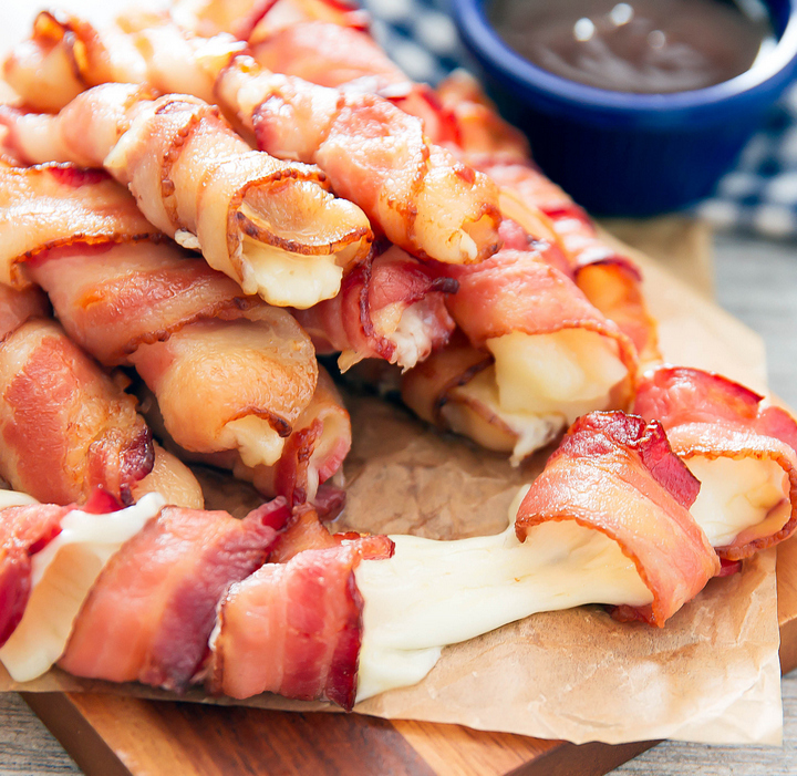 a close-up photo of bacon-wrapped cheese sticks with one cut in half