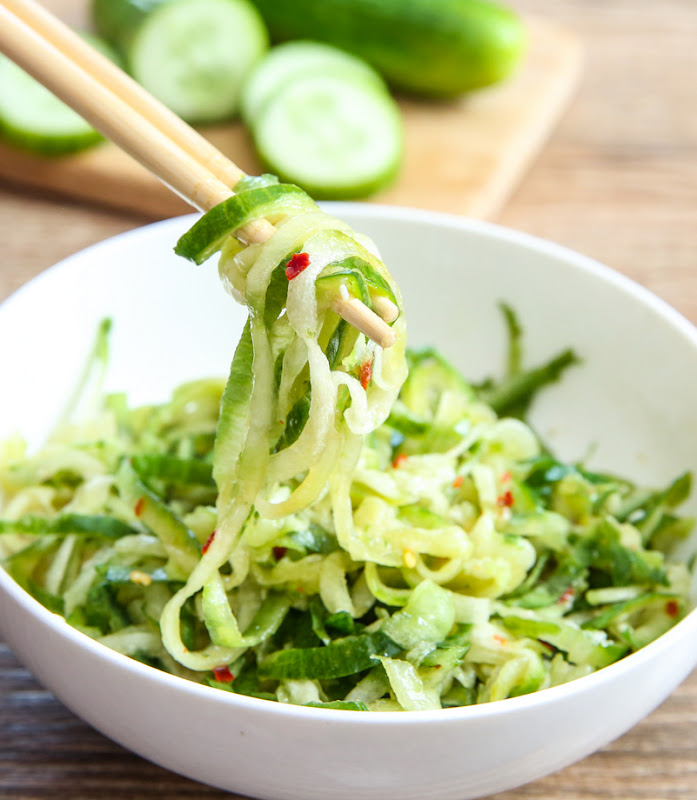 close-up photo of chopsticks holding cucumber noodles
