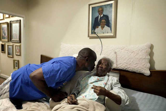 Greg Gunner, left, kisses his grandmother Mabel Bishop, 99, on Tuesday, 26 September 2017 in Port Arthur, Texas, in their home that was damaged by Hurricane Harvey. Gunner carried his grandmother, stricken with Alzheimer's disease, out of the house as the floodwaters rose, telling her they were going fishing to try to keep her calm. He voted for Hillary Clinton in November, and says the country's political divides have left him with little faith in the government's ability to get things done. But he believes the storm that wrecked his town is a preview of what global warming will bring if the nation's divided political sides don't find common ground to address it. 'The intensity of the destruction taking place these days, there's something going on. I think it's a wake-up call, to say, hey, what's important? What's really important?' he said. 'Are you going to work together, or are you going to pull each other apart?' Photo: David Goldman / AP