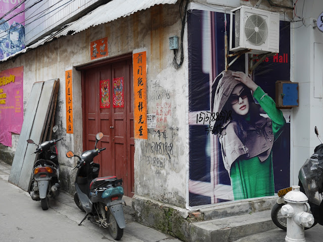 a fashionable advertisement on the wall of an older building with red doors in Yangjiang