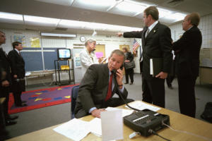 Color photo of Deputy Assistant Dan Bartlett pointing to news footage of the World Trade Center, President George W. Bush gathers information about the attack Tuesday, Sept. 11, 2001, from a classroom at Emma E. Booker Elementary School in Sarasota, Fla