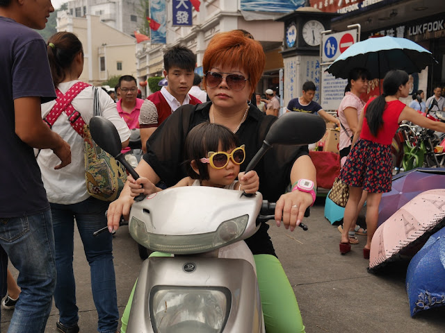 girl and woman wearing sunglasses riding a scooter in Zhongshan, Guangdong