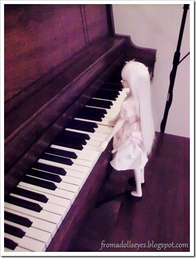 A bjd trying to play a piano.