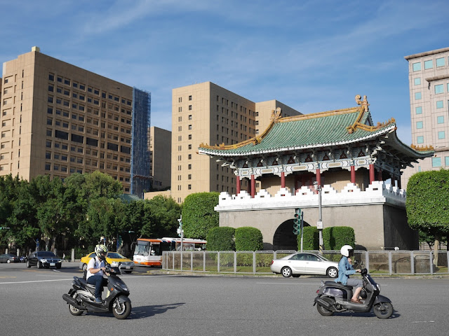 people riding motor scooters and driving cars past Taipei's East Gate