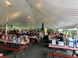 Corcoran Management Company employees sitting at picnic tables together under a tent at Kimball Farm