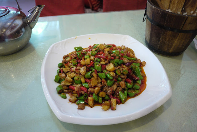 spicy dish next to a wooden bucket of rice in Chengdu, Sichuan