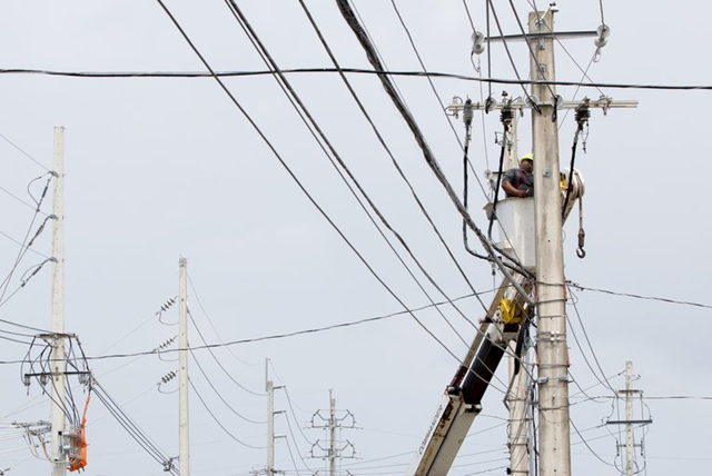A worker repaired a power line in San Juan, P.R., on Wednesday, 18 April 2018. A major failure had knocked out the electricity across Puerto Rico. Photo: Jose Jimenez Tirado / Getty Images