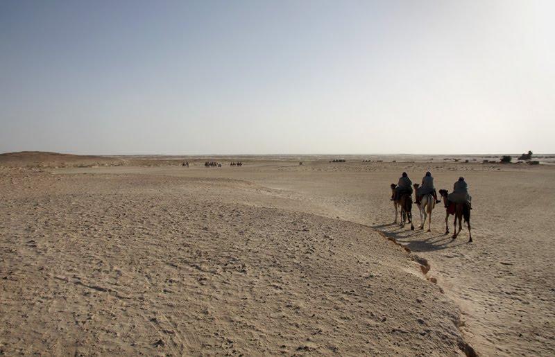 Vazio do deserto com três cavaleiros sobre a direita