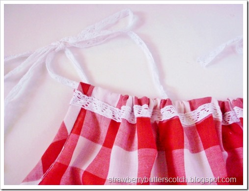 Red and white gingham print pillow case dress for baby.  Close up on the lace.