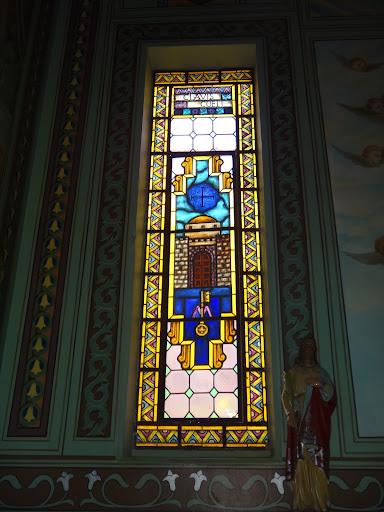 """Vitral Esquerdo. Logo na parte superior tem-se a inscrição em latim """"Clavis Coeli"""" que quer dizer """"Chave do Céu"""". Maria é o caminho para o céu. Tem-se no vitral as portas do Paraíso cuja chave se tem a inscrição da letra """"M"""", de Maria."""