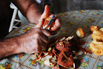 The head of the house peels food for our meal in the Santiago De Cuba homestay