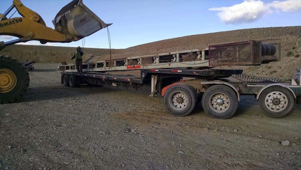 heavy loader unloading a rockscreen from flatbed trailer