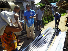 Several people standing around sheets of roofing materials