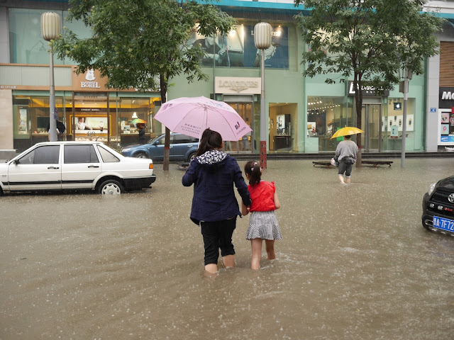 woman and girl with an umbrella walking on a flooded street in Taiyuan, China