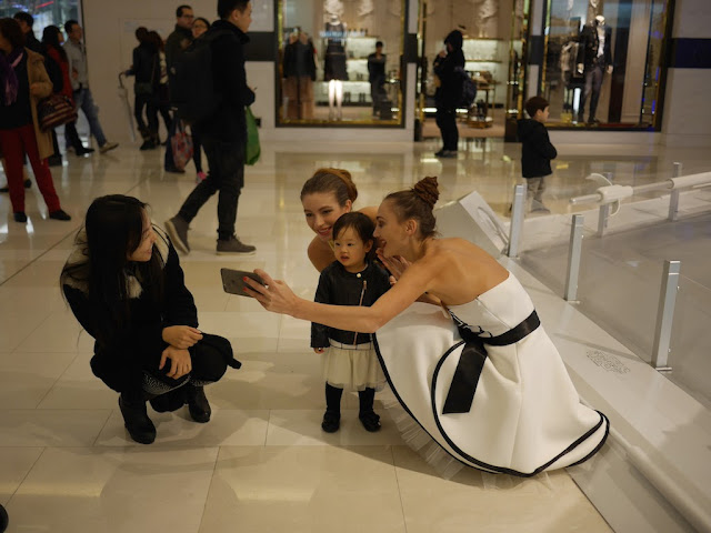 little girl posing for a photo with two female models at the Star Wars promotion at the IAPM shopping center in Shanghai