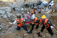 Palestinian rescue officers remove a body from the rubble of a building where at least 20 members of the Al Najar extended family were killed, including at least 10 children, by an Israeli strike in Khan Younis, in the southern Gaza Strip, Saturday, July 26, 2014, according to Palestinian health official Ashraf al-Kidra. A brief cease-fire Saturday in the Gaza war between Israel and Hamas militants allowed thousands to return home to see the destruction. (AP  Photo/Eyad Baba)