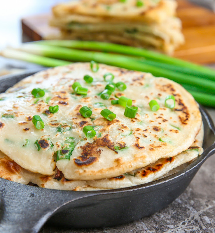 a close-up photo of scallion pancakes garnished with sliced scallions stacked in a skillet