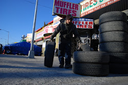 A worker at a tire shop wheels out some stock on an early morning in February.
