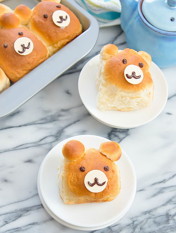 two bear-shaped milk bread rolls on plates with more rolls in a pan
