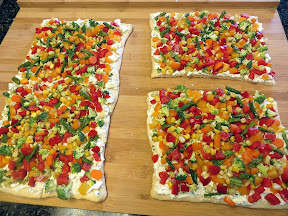 Chilled Vegetable Pizza recipe: Veggie Crescent Bites with cream cheese/sour cream/dill and chives on crescent roll and topped with pretty veggies