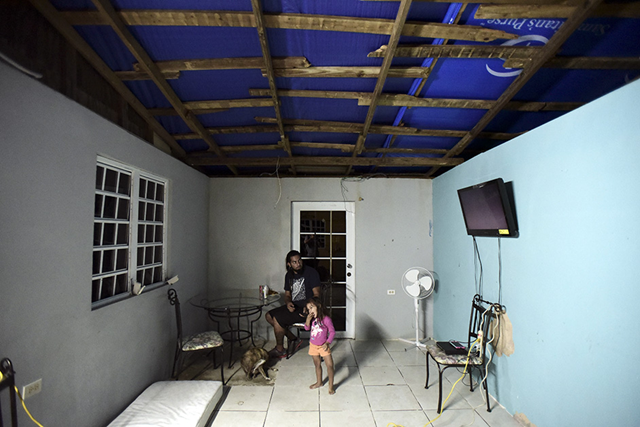 In this 21 December 2017 photo, two year-old Yeinelis Oliveras González accompanies her father, Luis Oliveras, while eating dinner, in Morovis, Puerto Rico. The light blue glow cast by a tarp that covers half their roof, a donation from a church, has already dissipated. The other half of the roof is recycled zinc pieces that Jose Luis Gonzalez pieced together for them. FEMA has not given them any assistance. Photo: Carlos Giusti/AP Photo