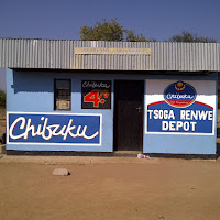 A typical Chibuku stand, Chibuku is the cheap but popular alcoholic beverage. Usually there are 5 - 10 men lounging around outside