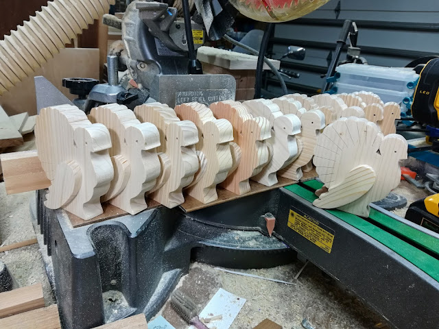 Handmade wood unfinished layered Thanksgiving turkey cutouts ready for painting sitting on my Hitachi miter saw.