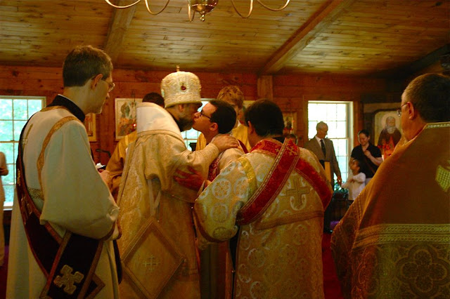 Vladyka embraces Nilus and congratulates him on his ordination.