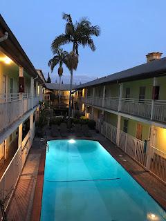 Bakgård til en bygning i to etasjer, begge med dører mot en utvendig gang. Et opplyst svømmebasseng midt i bildet.