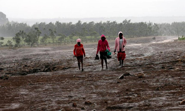 Residents walk in the rain at the Solai farm after their dam burst its walls, overrunning nearby homes, in Solai town near Nakuru, Kenya, 10 May 2018. Photo: Thomas Mukoya / REUTERS