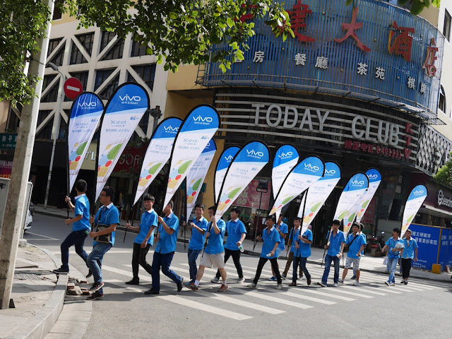group of people marching down the street wear Vivo shirts and hold Vivo promotional signs
