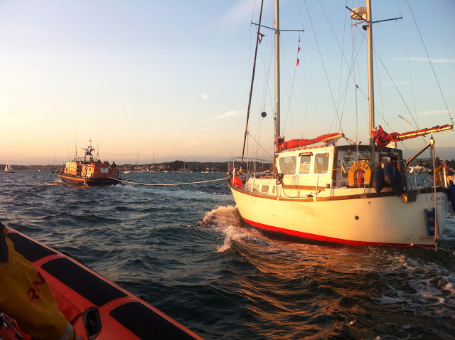Poole all-weather Tyne class lifeboat towing a 9.5m motor sailing vessel that had overheated, with the owners fearing that it had caught fire. Poole ILB is alongside monitoring the situation. 19 August 2013 Photo: RNLI/Dave Riley