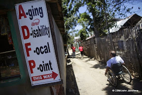 A man (wheelchair user) next to a sign saying Aging and Disability Focal Point