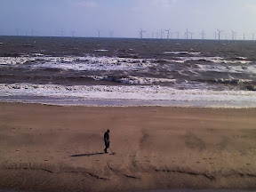 beach and sea with wind turbines in distance with amusing metal detector hobbyist and his rows of footprints