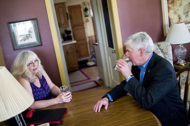 Michigan Gov. Rick Snyder, right, drinks filtered Flint, Michigan, tap water with Flint resident Cheryl Hill while listening to her concerns with the city's ongoing water crisis at her home Monday, 18 April 2016. Photo: Jake May / The Flint Journal-MLive.com